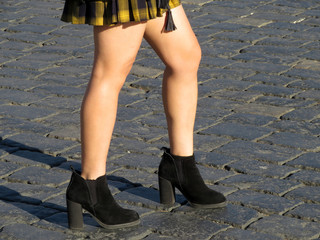 Slender girl in a short plaid skirt and high-heeled shoes. Naked female legs on the street background, autumn fashion, sexy body