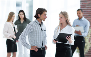 businessman and business woman standing in a modern office.