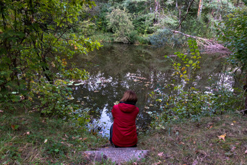 A girl in a red jacket sits on the shore of a forest lake