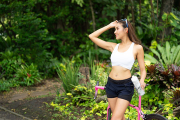 Portrait of young sport girl with pink bicycle hoding bottle of water resting after exercise