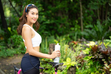 Smiley beautiful young sport girl holding bottle of water