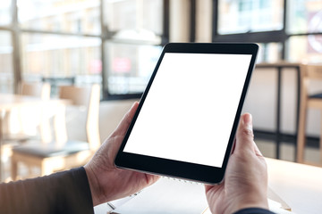 Mockup image of hands holding and using black tablet pc with blank white desktop screen with notebooks on the table