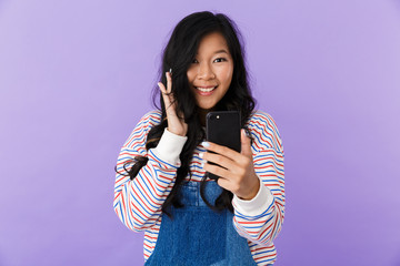 Happy young asian beautiful attractive woman posing isolated indoors using mobile phone.