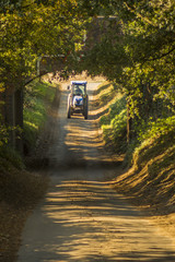 Blue tractor going under the bridge on a rural lane