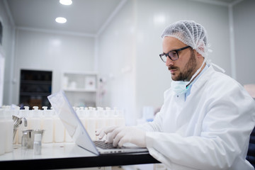 Technologist using laptop for entering data of test results while sitting in the lab. Next to him bottles filled with cosmetic product.
