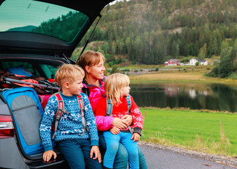 happy family- mother with son and daughter- travel by car