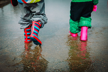 kids in rubber boots playing in water puddle
