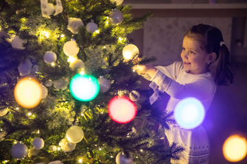girl  decorates a Christmas tree