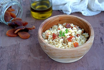 Couscous with dried apricots and fried onions in a wooden bowl. Traditional Moroccan dish. Healthy food.