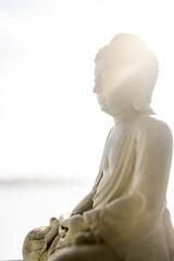 Götzenstatue eines Buddha oder Brahmanen, mit Lensflaire und Gegenlicht