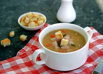 Yellow pea soup with smoked ham, pearl barley and carrots on a dark background. Served with white wheat bread croutons