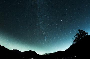 魚眼レンズで撮影した山と満天の星空