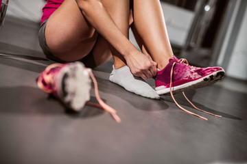 Woman preparing to worka out in a gym. Focus on sneaker.
