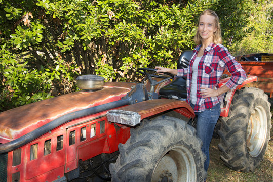 Young woman with tractor in olive grove