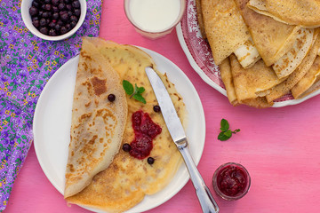 Sweet thin pancakes crepes served with raspberry jam