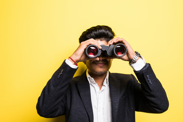 An Indian businessman in his late thirties looking through binoculars isolated on yellow background