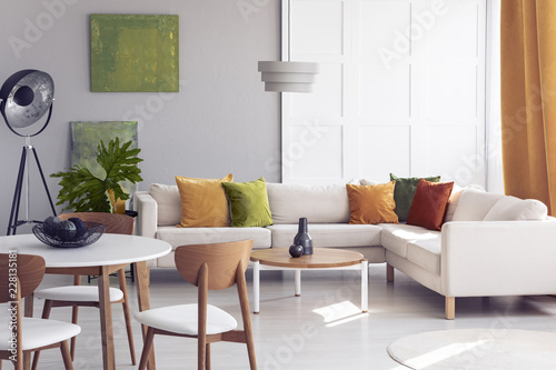 Wooden Chairs At Table In Bright Living Room Interior With Green