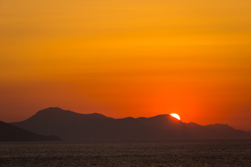 Dramatic sunset over sea surface, Greece Peloponnese. Romantic sunset scenic ocean view in vast Aegean