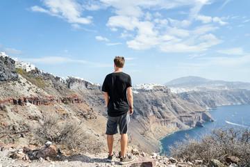 Mann steht auf einem Berg und genießt die schöne Aussicht über die Küste von Santorini