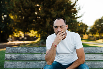 Man covering mouth in park