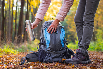 Traveler is taking thermos out from her backpack. Woman is wearing hiking boot and standing on footpath at autumn forest.