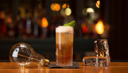 Cocktail Bar Stimmungsbild dunkel mit Glas Glühbirne Schaum Minzblatt und Eiswürfel