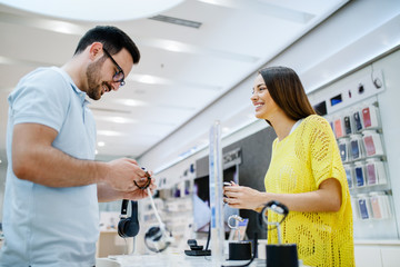 Happy couple holding smart watches while standing in tech store.
