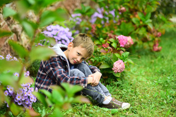 A garden is a grand teacher. Small child relax in garden. Small child enjoy flowers blossoming in garden. Walk in a garden to know a beauty