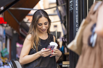 Woman with drink and smartphone near outdoor cafe