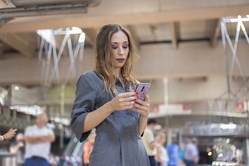 Woman using smartphone on railway station