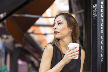 Woman with drink near outdoor cafe