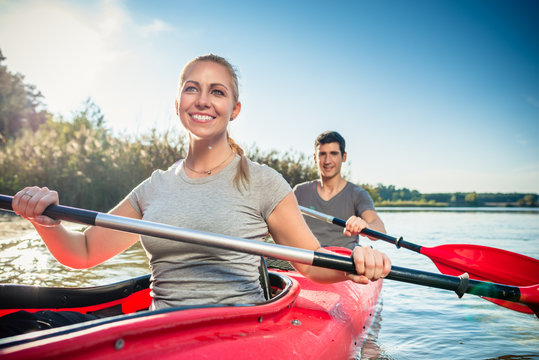 Smiling young woman kayaking with her boyfriend on lake