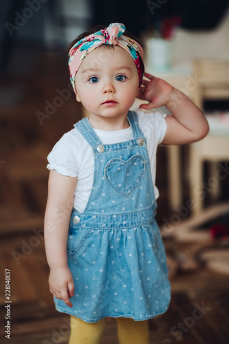 43f1b9477 Portrait of little cute and pretty girl in jeans dress and bandage ...