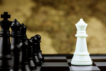White queen chess stand encounter black enemy on a chessboard. - Business winner and fight concept.