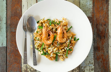 Fried noodle Thai style with prawns on wood table top view