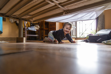 Cheerful toddler looking under bed