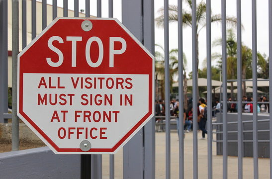A sign at a closed campus advises visitors to sign in