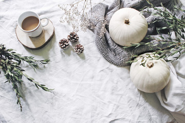 Autumn styled photo. Feminine Halloween desktop scene. Cup of coffee, eucalyptus, pine cones, white pumpkins and gypsophila flowers. Table background. Thanksgiving. Flat lay, top view.