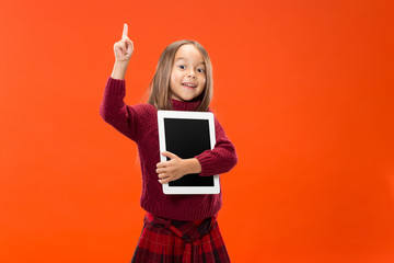 Little funny girl with tablet on studio background. She showing something and pointing at screen.