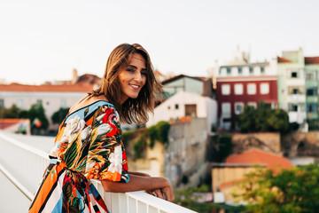 Smiling happy woman on bridge against cityscape