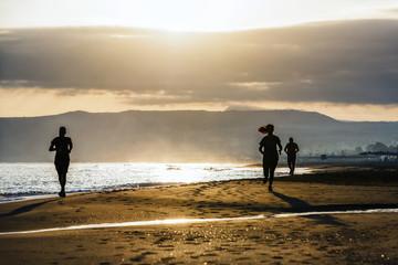 couple running on the beach at sunrise