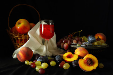 Fruit and a glass of red wine on a dark background