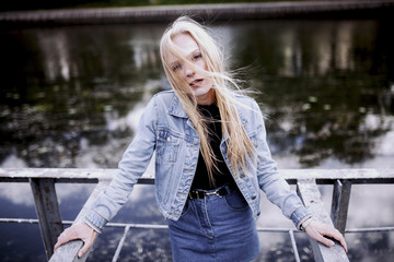Portrait of young woman with blond tousled hair standing against pond in city