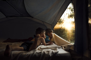 Brothers with hand on chin looking away while relaxing in tent
