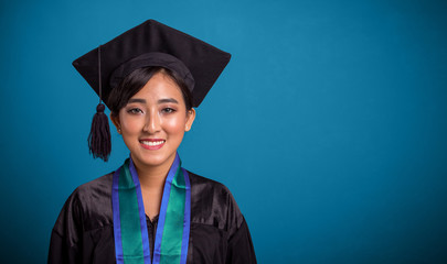 Happy graduating Asian student closeup over blue