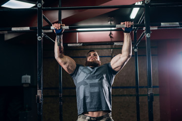 Muscular caucasian bearded man doing pull-ups and training his biceps and back in gym.