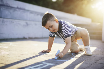 Boy drawing with chalk on footpath at sunset