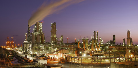 Illuminated petrochemical plant against sky during sunset