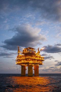 Illuminated oil exploration platform in sea against cloudy sky