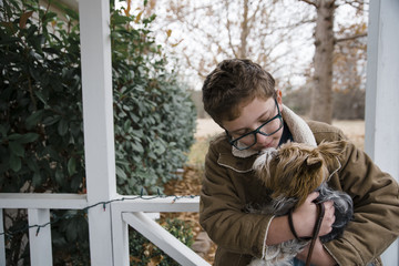 Boy carrying dog while standing against trees in porch